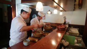 料理人がクエ鍋を取り分けています